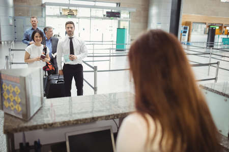 queue: Passengers waiting in queue at check-in counter in airport terminal LANG_EVOIMAGES