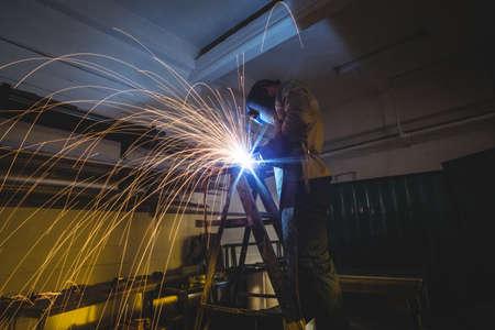 blacksmith: Male welder working on a piece of metal in workshop LANG_EVOIMAGES