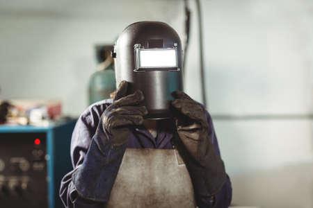 blacksmith: Welder holding welding helmet in workshop LANG_EVOIMAGES