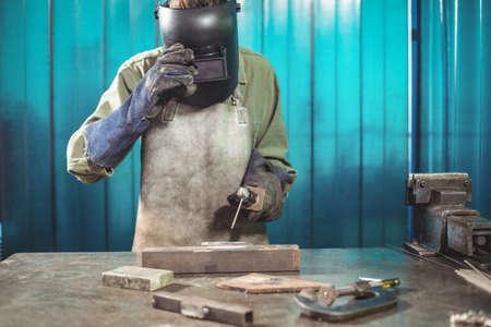 blacksmith: Female welder holding welding arch in workshop