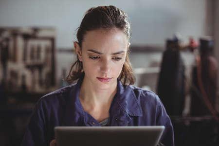 technology: Female welder holding digital tablet in workshop LANG_EVOIMAGES