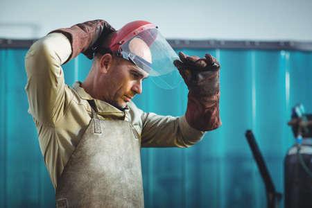 blacksmith: Male welder wearing protective helmet in workshop