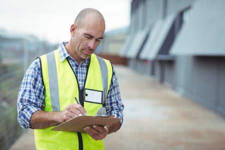 competencias laborales: Trabajador de la construcción en un portapapeles fuera de la oficina