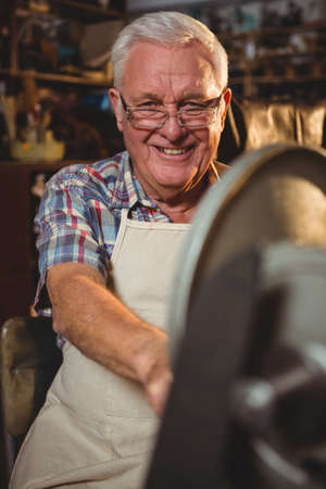 70s: Portrait of smiling shoemaker working in workshop