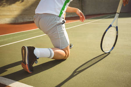 man kneeling: Man kneeling in the court while playing tennis on a sunny day
