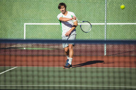 Man playing tennis in the court on a sunny day LANG_EVOIMAGES