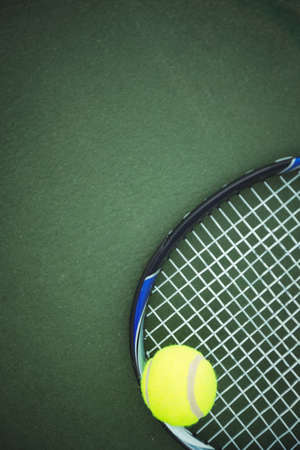 athleticism: Tennis ball and racket lying on the ground in the court LANG_EVOIMAGES