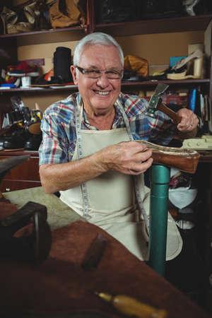hammering: Portrait of shoemaker hammering on a shoe in workshop LANG_EVOIMAGES