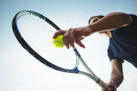 Man with tennis racket ready to serve in the court LANG_EVOIMAGES