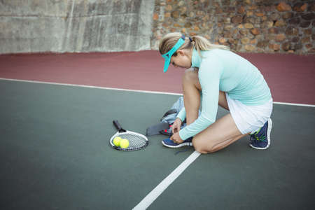 tennis shoe: Female tennis player tying her shoe lace in the court