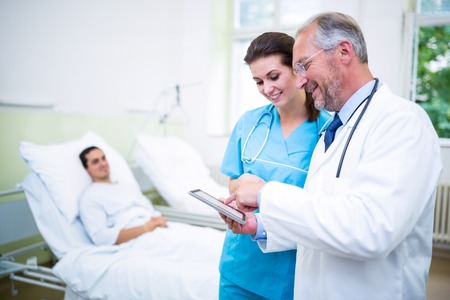 Doctor and nurse discussing on digital tablet in hospital