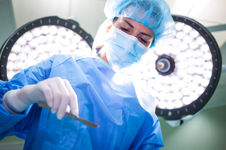 surgical light: Female surgeon holding medical equipment in operation room at hospital
