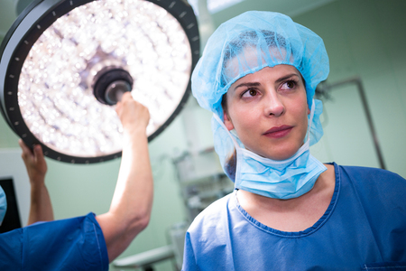 surgical mask woman: Female surgeon standing in operation room Stock Photo
