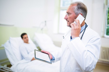 Doctor talking on mobile phone and talking on mobile phone in hospital Stock Photo