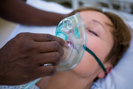 oxygen mask: Nurse placing an oxygen mask on the face of a patient in hospital Stock Photo