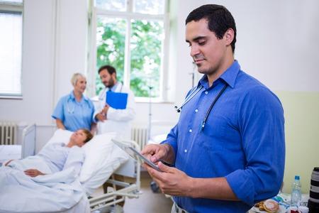 Confident doctor using digital tablet in hospital