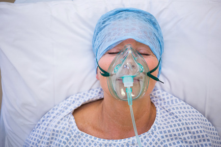 oxygen mask: Patient wearing oxygen mask lying on bed in hospital Stock Photo