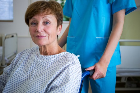wheel chair: Portrait of patient sitting on wheel chair with nurse standing behind in hospital Stock Photo