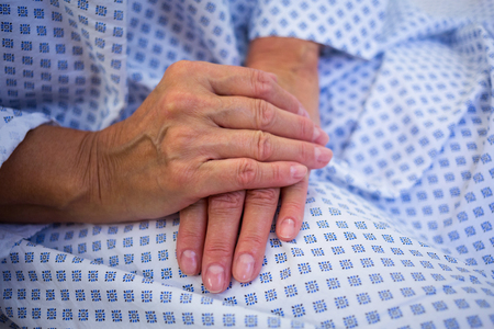 discouraged: Close-up of senior patients hands in hospital room Stock Photo