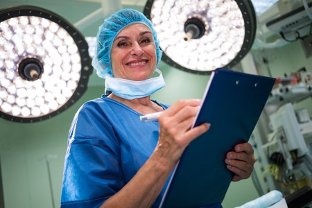 operation room: Portrait of smiling female surgeon writing on clipboard in operation room at hospital