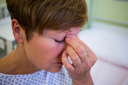 Close-up of tensed senior patient in hospital room