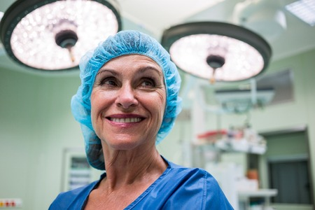surgical light: Smiling surgeon standing in operation room at hospital Stock Photo