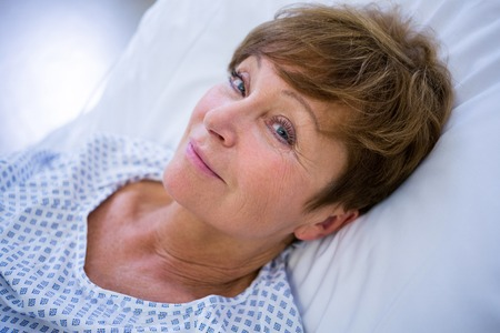 hospitalized: Portrait of smiling patient lying on bed in hospital Stock Photo