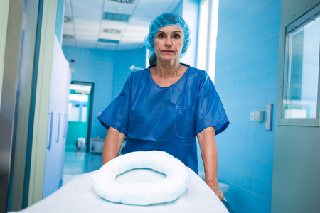 surgical cap: Portrait of nurse pushing empty stretcher in hospital Stock Photo