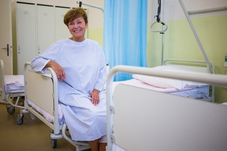 afflict: Portrait of smiling senior patient sitting on a bed in hospital room Stock Photo