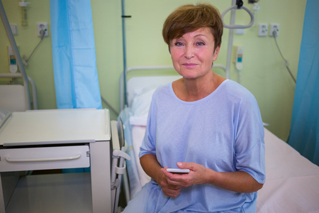 afflict: Portrait of senior patient sitting on a bed in hospital room