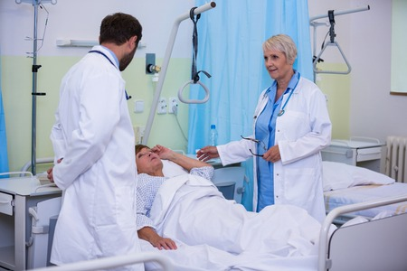afflict: Doctors talking to a senior patient in hospital room Stock Photo