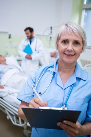 Portrait of smiling nurse writing on clipboard in hospital room Stock Photo