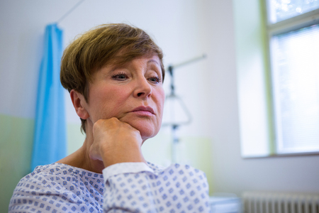 Close-up of sad senior patient sitting on a bed in hospital room Stock Photo