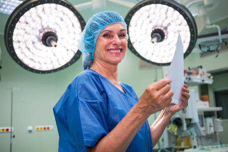 surgical light: Portrait of smiling surgeon holding report in operation room at hospital Stock Photo
