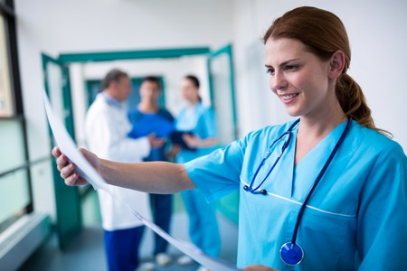 examining: Smiling surgeon examining a report in hospital Stock Photo
