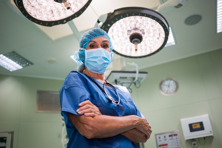 operation room: Portrait of surgeon standing with arms crossed in operation room at the hospital