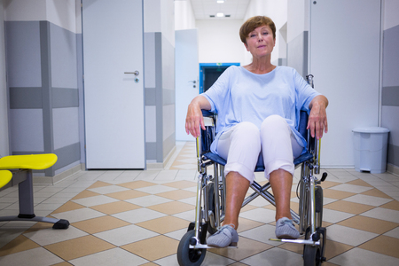 afflict: Sad senior patient sitting on a wheelchair in hospital