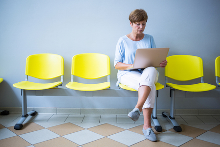 afflict: Patient sitting with report in a waiting room of a hospital