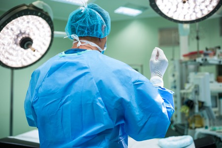 Rear view of surgeon standing in operation room at hospital Stock Photo
