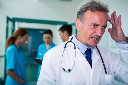 tensed: Tensed doctor standing in corridor at hospital Stock Photo