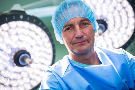 scrub cap: Portrait of surgeon standing in operation room at the hospital Stock Photo