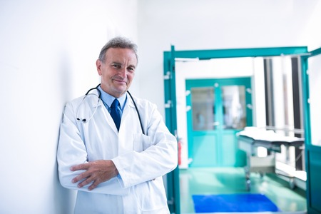 Portrait of doctor standing with arms crossed in hospital Stock Photo