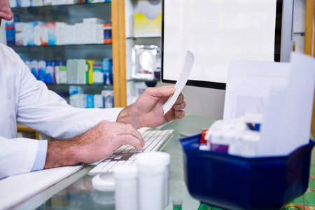 entries: Pharmacist making entries on computer in pharmacy
