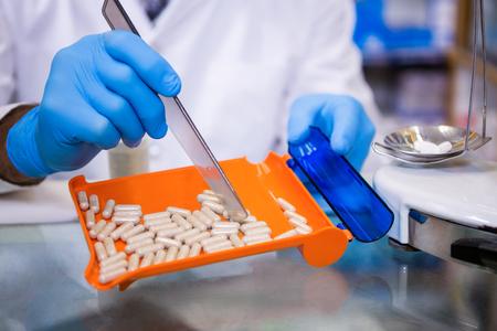 Lékárník uvedení pilulky v kontejneru v lékárně