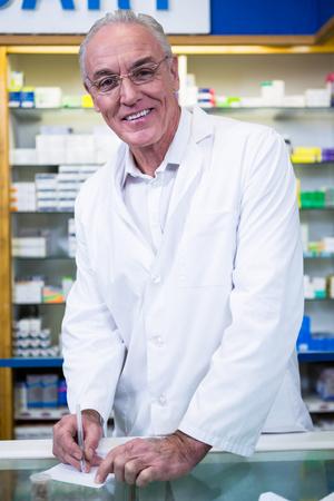 recetas medicas: Portrait of pharmacist writing prescriptions for medicines in pharmacy Foto de archivo