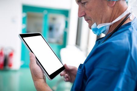 Surgeon using digital tablet in hospital corridor