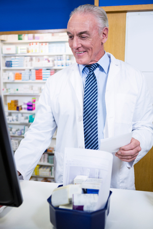 Pharmacist making entries on computer in pharmacy