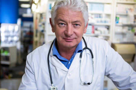 dispensary: Portrait of pharmacist in lab coat at pharmacy Stock Photo