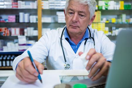recetas medicas: Pharmacist writing prescriptions for medicines in pharmacy