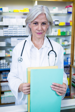 Portrait of pharmacist holding files in pharmacy
